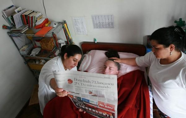 Leide, com suas cuidadoras Eliane e Ivania, durante a leitura do Jornal, atividade realizada diariamente. Foto de Marcelo Min.