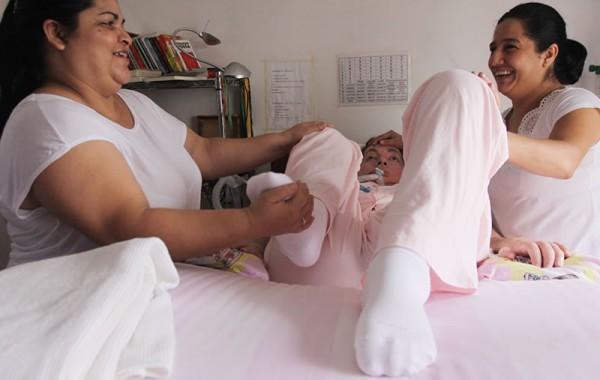 Ivania e Eliane, cuidadoras, alongando as pernas de Leide. Foto de Fernanda Prado.
