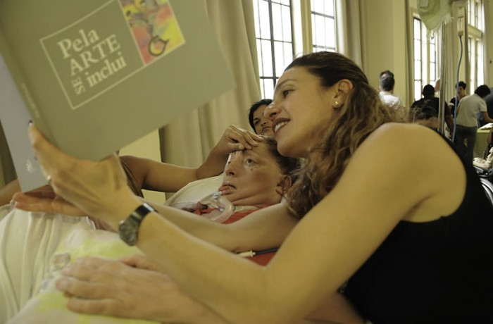 """Leide Jacob, filha de Leide, mostrando para ela o livro """"Pela Arte se Inclui"""", no qual ela é destaque em um capítulo, lançado pela Secretaria Estadual de Cultura em 2012. Foto de Claudio Belli."""