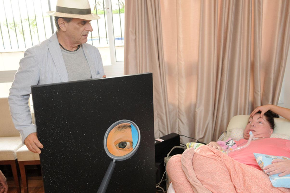 """Antonio Peticov mostrando o quadro """"Cosmic eyes"""", que compoe o projeto da capa do livro, para Leide."""