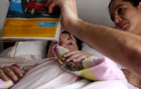 Leide, com sua auxiliar Eliane, atenta a revista mostrada por seu filho Cesar. Foto de Fernanda Prado.
