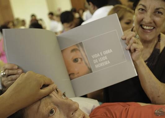 """Jandyra Viegas, amiga de Leide, mostrando o capítulo que destaca Leide, no livro """"Pela Arte se Inclui"""", em 2012. Foto de Claudio Belli."""